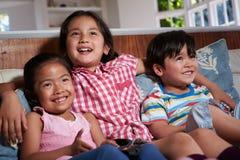 三个亚裔孩子坐一起看电视的沙发 免版税库存照片