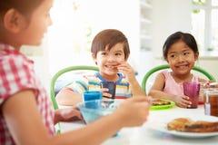三个亚裔孩子食用早餐一起在厨房 免版税图库摄影