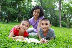 三个亚洲孩子有好时光在公园 免版税库存图片