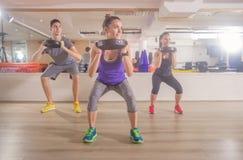 三个人健身健身房蹲坐衡量手 免版税库存图片