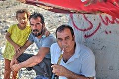 三个人在树荫,一下坐抽水烟筒 免版税库存图片