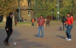 三个人在米兰公园踢橄榄球 库存图片