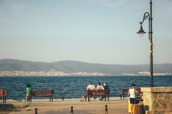 三个人坐在Nessebar散步的一条长凳并且看晴朗的海滩 库存图片