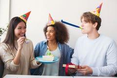 三个人庆祝生日 他们戴滑稽的帽子 当人有一个礼物时,女孩拿着有蛋糕的一块板材 库存照片