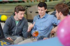 三个人有交谈在保龄球中心 库存图片