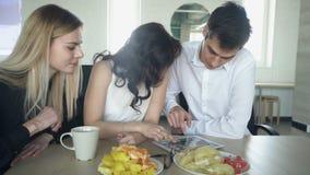 三个人有观看的片剂早餐用果子和休息 影视素材