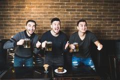 三个人用啤酒在目标前高兴他们喜爱的队胜利在客栈 客栈饮料啤酒 免版税图库摄影