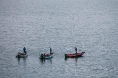 三个人钓鱼在Kawaguchiko lak的小汽船 库存图片