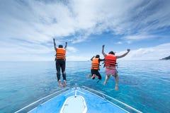 三个人从速度小船在Ta池氏, Similan海岛泰国跳 库存照片