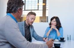 三个企业同事开会议一起在办公室 免版税库存图片