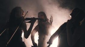 三个使用在一个密谈室的了不起的女孩小提琴手 光通过烟做他们的方式 r 股票视频