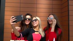三个俏丽的女孩shopaholic在购物以后做selfie 采取selfie的可爱的俏丽的妇女在购物以后 女孩 影视素材