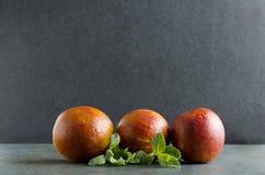 三个健康的血桔子和新鲜薄荷黑暗的土气表面上反对黑背景 免版税图库摄影