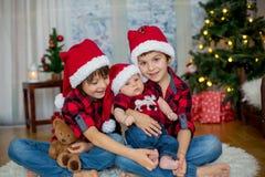 三个兄弟圣诞节画象有坐圣诞老人的帽子的  免版税库存图片