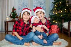 三个兄弟圣诞节画象有坐圣诞老人的帽子的  库存照片