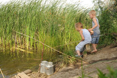 三个兄弟在一个安静的死水村庄聚集钓鱼在结尾杆 免版税库存照片