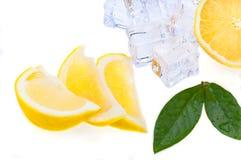 三个切片与绿色叶子的新鲜,明亮的水多的冷的冰柠檬和立方体,在白色背景 查出 免版税库存照片