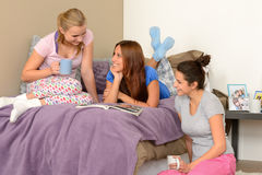 三个十几岁的女孩谈话在睡衣派对 免版税图库摄影