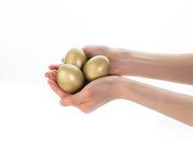 三个发光的金黄鸡蛋 免版税库存图片