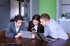 三个同事、女性和两个年轻人在社会网络坐 库存图片