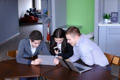 三个同事、女性和两个年轻人在社会网络坐 免版税库存图片