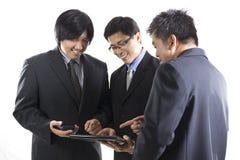 三个商人会议和使用移动电话 库存图片