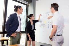 三个商人在看报告和分析与谈话的现代办公室在会议室 库存图片