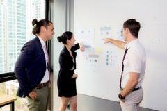 三个商人在看报告和分析与谈话的现代办公室在会议室 免版税库存照片