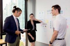 三个商人在看报告和分析与谈话的现代办公室在会议室 库存照片