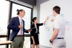三个商人在看报告和分析的现代办公室 免版税库存图片