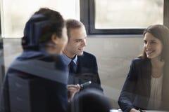 三个商人坐和谈论在业务会议上 图库摄影