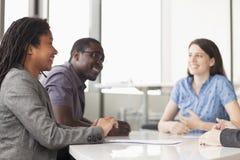 三个商人坐在会议桌上和谈论在业务会议期间 免版税库存图片