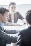 三个商人坐在桌上和开业务会议在办公室 库存图片