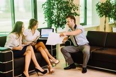 三个商人坐有的沙发拿着文件夹和交谈 图库摄影