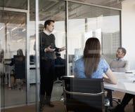 三个商人坐,站立和谈论在业务会议期间 库存照片