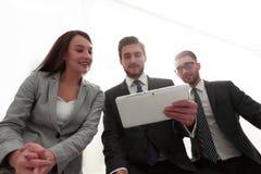 三个商人看一台片剂个人计算机 免版税库存图片