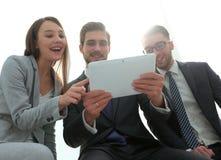 三个商人看一台片剂个人计算机 库存照片