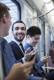 三个商人连续坐和谈话在地铁 免版税库存照片