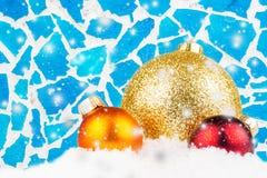三个圣诞节球和蓝色马赛克背景与雪 免版税库存图片