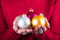 三个圣诞节球在红色knitt背景的女性手上  免版税库存图片