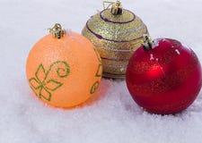 三个圣诞节球背景在雪的 库存照片