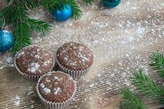 三个圣诞节蛋糕,冬天被雪包围住的木背景,蓝色 免版税库存照片