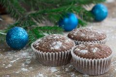 三个圣诞节蛋糕,冬天被雪包围住的木背景,蓝色 图库摄影