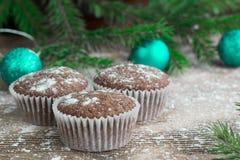 三个圣诞节蛋糕,冬天被雪包围住的木背景,绿色 库存照片