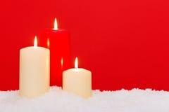 三个圣诞节蜡烛红色背景 免版税库存照片