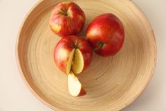 三个在一块木板材的红色苹果谎言 库存图片