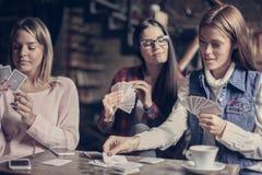三个在咖啡馆的女孩纸牌 免版税图库摄影