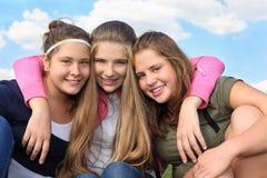 三个在天空背景的愉快的女孩拥抱  免版税库存图片