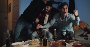 三个在电视的朋友观看的足球赛在家,欢呼最佳的足球队员 ?? 精神爱好者庆祝赢得 股票录像