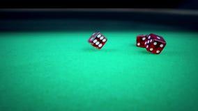 三个在绿色比赛赌博的桌上的红色模子辗压在黑背景,射击与慢动作,体育休闲的概念 股票录像